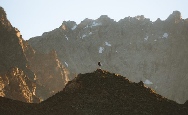 man standing atop a mountain