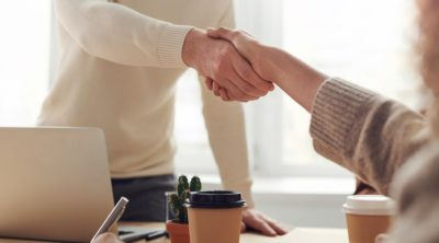 Image of two people shaking hands in an office