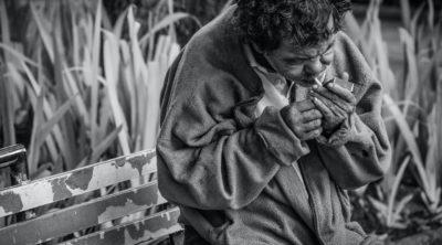 Man smoking cigarette on bench